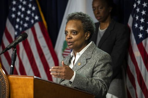 Dr. Ngozi Ezike, back right, director of the Illinois Department of Public Health, looks on as Mayor Lori Lightfoot speaks at the Thompson Center in Chicago during the daily update on the state's response to the coronavirus pandemic, Monday, March 30, 2020. (Ashlee Rezin Garcia/Sun-Times/Chicago Sun-Times via AP)