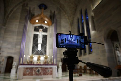 A smartphone is used to livestream a Eucharistic Adoration service at Saint Ann Catholic Church in Washington, Sunday night, March 29, 2020. The Archdiocese of Washington has temporarily halted all public Masses and gatherings in an effort to contain the spread of the coronavirus. This service was live streamed and those few who attended practiced social distancing. During Eucharistic Adoration the Blessed Sacrament is exposed, with the white Host visible within a golden display case called a monstrance.