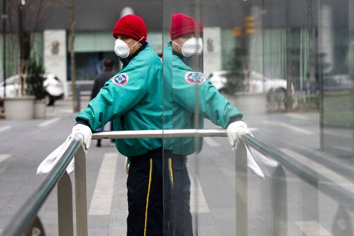 A worker in a protective face mask sanitizes hand rails at the entrances to a train station outside City Hall to help reduce the spread of coronavirus in Philadelphia, Monday, March 30, 2020.