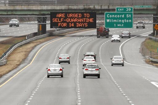 A highway sign urges out of state visitors to self-quarantine for 14 days if they plan on staying in Massachusetts due to the virus outbreak along Route 93 southbound in Wilmington, Mass., Monday, March 30, 2020. The new coronavirus causes mild or moderate symptoms for most people, but for some, especially older adults and people with existing health problems, it can cause more severe illness or death.
