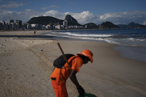 "Gloria Maria cleans the shore of an unusually empty Copacabana beach backdropped by the Sugar Loaf Mountain in Rio de Janeiro, Brazil, Thursday, March 26, 2020, as people stay indoors to help contain the spread of the new coronavirus. The 41-year-old city worker said that in her 10 years of work cleaning the beach, she never saw an empty beach on a sunny Thursday. ""It's terrible, people are dying in Europe due this virus,"" she added."