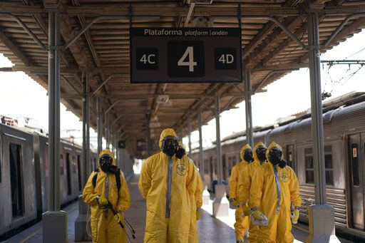 Soldiers stand in formation before disinfecting wagons for the new coronavirus at the central train station in Rio de Janeiro, Brazil, where trains connect cities within the state, Thursday, March 26, 2020. COVID-19 causes mild or moderate symptoms for most people, but for some, especially older adults and people with existing health problems, it can cause more severe illness or death.