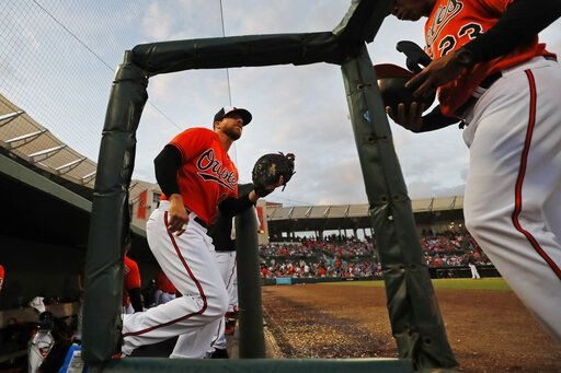 Baltimore Orioles first baseman Chris Davis, left, trots out of the dugout during a spring training baseball game against the Atlanta Braves, Tuesday, March 10, 2020, in Sarasota, Fla.
