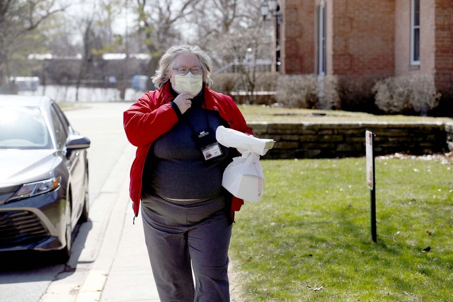 Thekla Metz, of Meals on Wheels, delivers to a residence in Highland Park on Wednesday. The number of food deliveries to older residents, people with disabilities and those in need has increased significantly during the COVID-19 outbreak, officials said, but so too has the number of volunteers.
