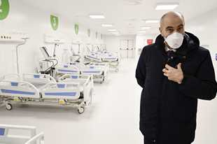 Director of Milan's Polyclinic hospital Ezio Belleri gives a tour to the media Tuesday of the newly built Ospedalefieramilano in Milan, Italy. Italian officials have unveiled a 200-bed intensive care field hospital at the Milan fairgrounds to help relieve the pressure on northern Italy's overwhelmed health care system from the coronavirus pandemic. The new coronavirus causes mild or moderate symptoms for most people, but for some, especially older adults and people with existing health problems, it can cause more severe illness or death.