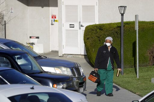 A health care worker leaves Cedar Mountain Post Acute nursing facility in Yucaipa, Calif., Wednesday, April 1, 2020. The Southern California nursing home has been hit hard by the coronavirus, with more than 50 residents infected, a troubling development amid cautious optimism that cases in the state may peak more slowly than expected.