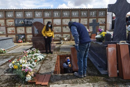 An undertaker prepares a grave during the burial of Rosalia Mascaraque, 86, during the coronavirus outbreak in Zarza de Tajo, central Spain, Wednesday, April 1, 2020. Intensive care units are particularly crucial in a pandemic in which tens of thousands of patients descend into acute respiratory distress. The new coronavirus causes mild or moderate symptoms for most people, but for some, especially older adults and people with existing health problems, it can cause more severe illness or death.