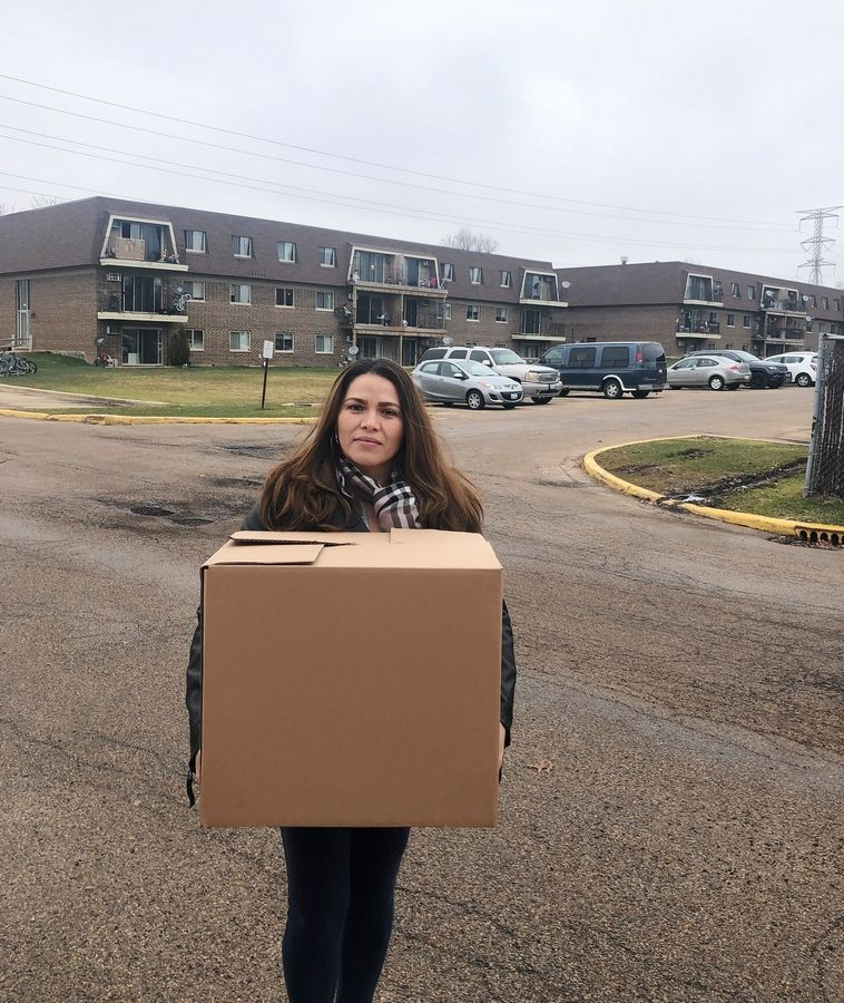 Gabriela Hernandez Chico, one of the organizers behind a DuPage mutual aid group, delivers food to residents at the Timber Lake Apartments complex in West Chicago during the coronavirus crisis.