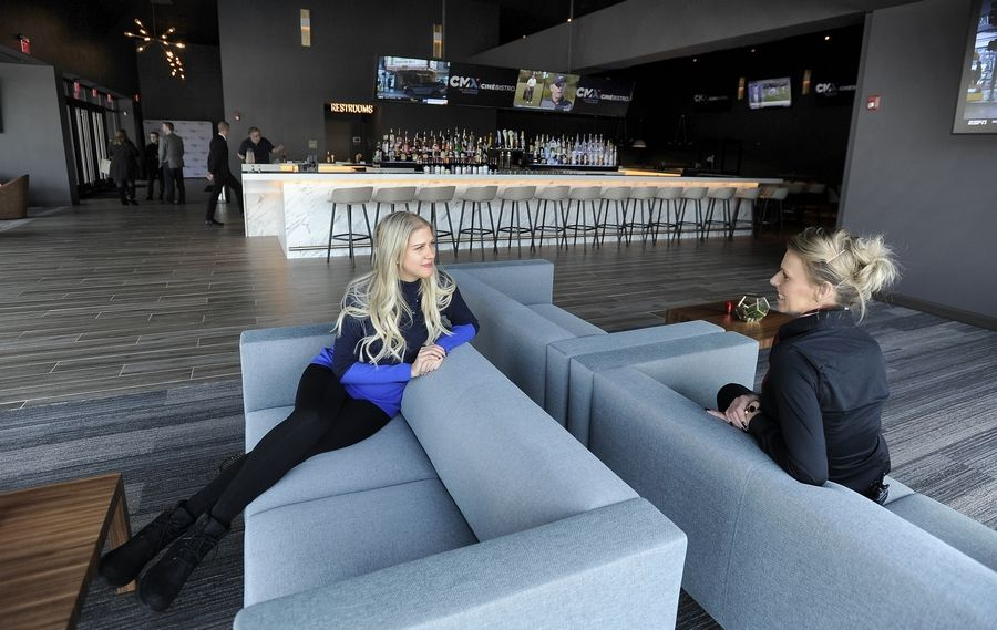 Laura Ginebra, left, and Paula Stanga get comfortable on the sofa in the bar area at CMX CinéBistro Wheeling at a special event before it opened in February.