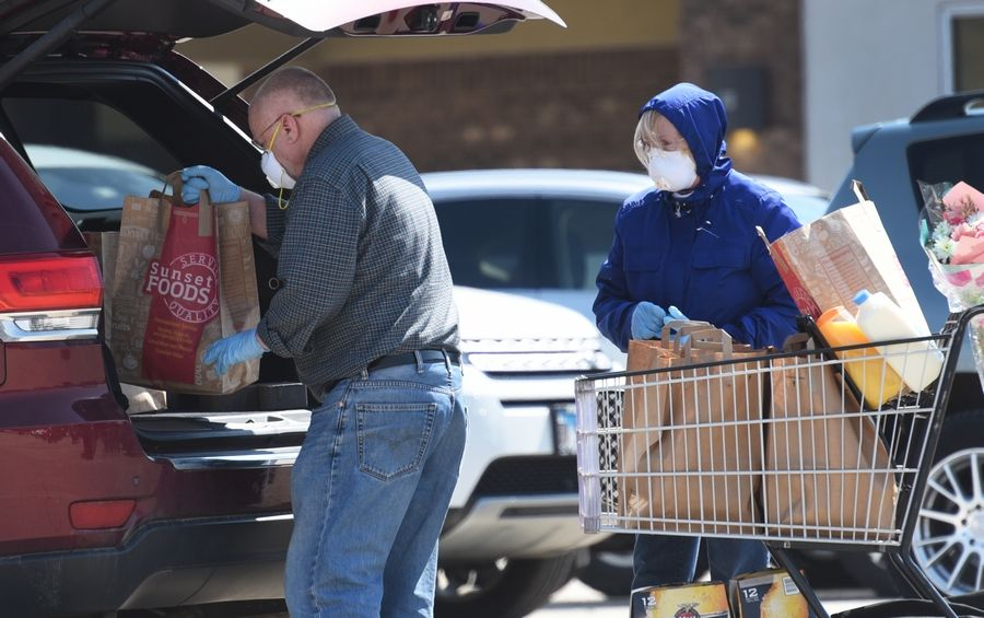 Libertyville residents Dan and Ginny Boggs wear protective masks and gloves during their grocery shopping trip to Sunset Food in Libertyville on Friday.