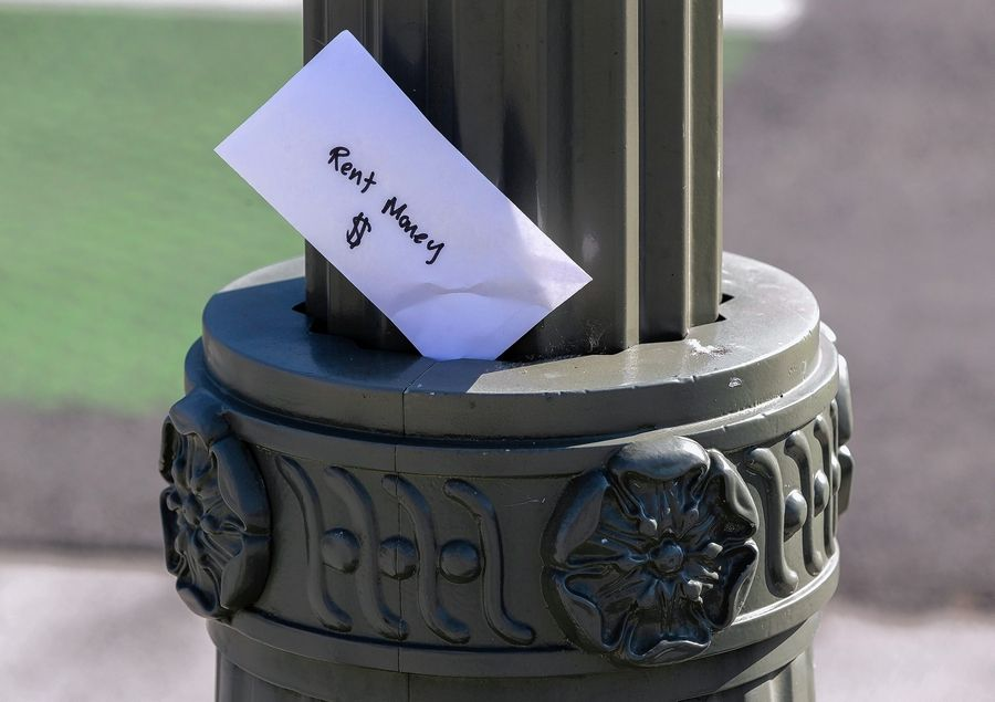 "A paper envelope written with the words ""Rent Money $ "" is left tucked in a lighting pole in the Boyle Heights east district of the city of Los Angeles on Wednesday, April 1, 2020."