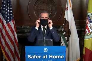 Courtesy of Office Mayor Eric Garcetti via Ap Los Angeles Mayor Garcetti puts on a protective face mask during his daily news conference Wednesday. Garcetti urged the city's 4 million people to wear masks when going outside.
