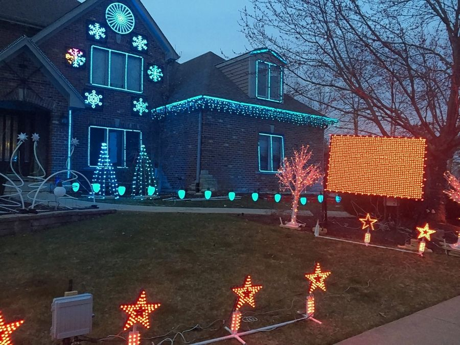 It's crunchtime for Brett Foy as he prepares a 12-minute music and light show at his house at 969 Ekman Drive in Batavia. He said it takes hours to program and sync lights to each song and, on Thursday night, a test run showed an illuminated snowflake, upper left, and other decorations needed some tweaking.