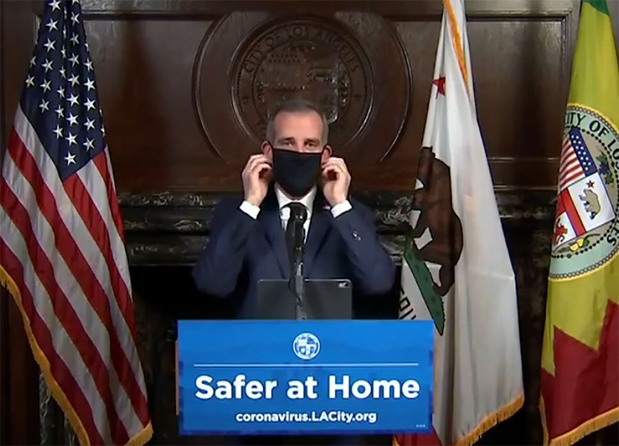 Courtesy of Office Mayor Eric Garcetti via ApLos Angeles Mayor Garcetti puts on a protective face mask during his daily news conference Wednesday. Garcetti urged the city's 4 million people to wear masks when going outside.