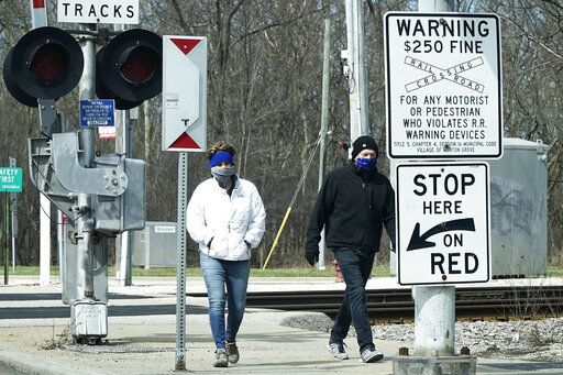People cover their faces with cloths as they walk on the sidewalk in Morton Grove, Ill., Sunday, April 5, 2020. The new coronavirus causes mild or moderate symptoms for most people, but for some, especially older adults and people with existing health problems, it can cause more severe illness or death.