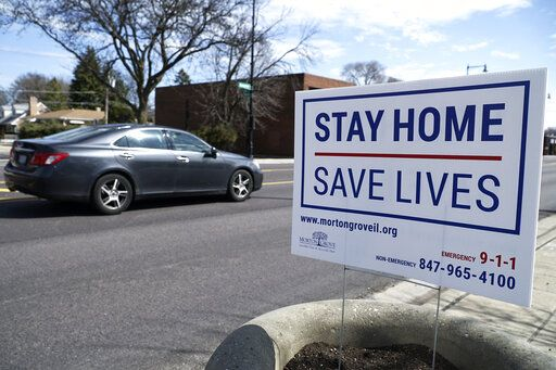 A sign encouraging people to stay home is seen in Morton Grove, Ill. Sunday, April 5, 2020, amid the  coronavirus outbreak.