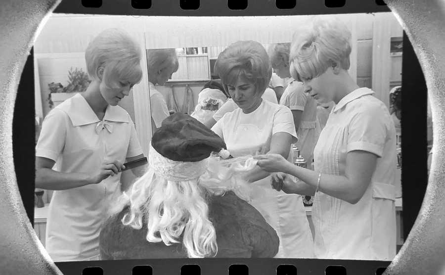 The Daily Herald Archives, Assignment # 5,395, Bob Strawn photo: Santa Claus invaded the feminine precincts of Duchess Beauty Salon in Rolling Meadows to get a glamour treatment before his official arrival at Randhurst Shopping Center. As Santa sat under the dryer, regular customers appeared to be speculating whether it would be worth while to tell him what they would like for Christmas in December of 1966.
