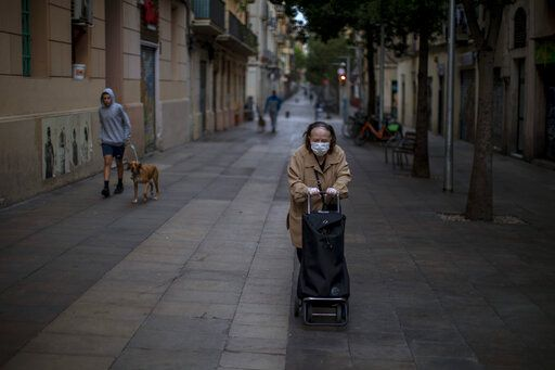 A woman pushes her cart along the street during the COVID-19 virus outbreak in Barcelona, Spain, Tuesday, April 7, 2020. Spain is recording again a rise of daily coronavirus infections and deaths for the first time in five days, a result consistent with previous Tuesdays when a weekend backlog of tests and fatalities are reported. The new coronavirus causes mild or moderate symptoms for most people, but for some, especially older adults and people with existing health problems, it can cause more severe illness or death.