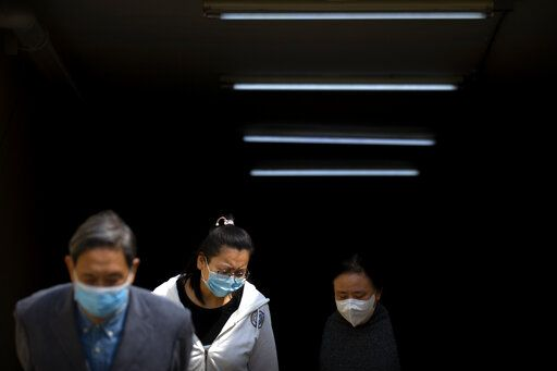 People wear face masks as they exit a subway station in Beijing, Tuesday, April 7, 2020. China on Tuesday reported no new deaths from the coronarivus over the past 24 hours and just 32 new cases, all from people who returned from overseas.