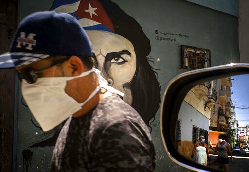 "A man wearing a mask walks alongside a mural of Ernesto ""Che"" Guevara as other pedestrians are reflected in the side-view mirror of a car in Havana, Cuba, Tuesday, April 7, 2020. Cuban authorities are requiring people use masks outside their homes as a measure to help contain the spread of the new coronavirus."