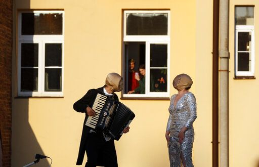 Street musicians entertain residents, as people stay in their houses to counter the spread of coronavirus, in Prague, Czech Republic, Tuesday, April 7, 2020. The Czech Republic's government has incorporated dramatic restrictive measures to try and stem the spread of the new coronavirus called COVID-19. The new coronavirus causes mild or moderate symptoms for most people, but for some, especially older adults and people with existing health problems, it can cause more severe illness or death.