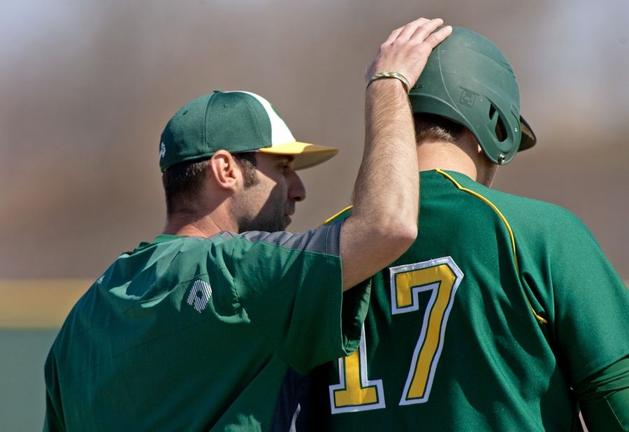 Waubonsie Valley head baseball coach Bryan Acevedo encourages Brandon Petersen, right, who prepares to hit against Naperville Central.