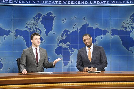 "This Feb. 29, 2020 photo released by NBC shows Colin Jost, left, and Michael Che during the Weekend Update sketch on ""Saturday Night Live"" in New York. The show will be back on the air this weekend with a show that abides by social distancing rules. NBC says the comedy sketch show will include include a 'œWeekend Update'� news segment and original content from 'œSNL'� cast members. The material will be produced remotely, in compliance with efforts to limit the spread of the coronavirus. (Will Heath/NBC via AP)"