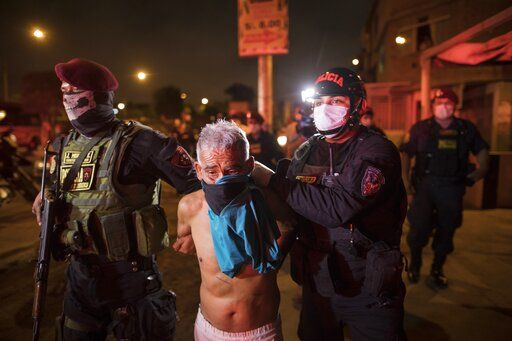Policemen detain a man for violating the curfew declared by the government amid coronavirus concerns in El Callao, on the outskirts of Lima, Peru, Wednesday, April 8, 2020.