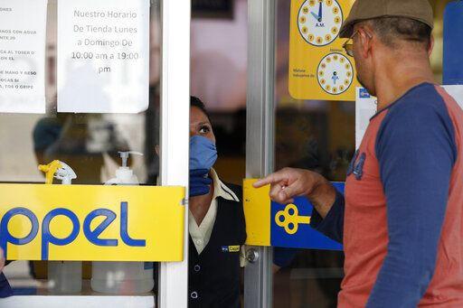 An employee controls access to a Coppel department store, where shoppers were being asked to wait in line to enter a few at a time, and to use hand gel and maintain social distancing, in Mexico City, Wednesday, April 8, 2020. Mexico's government announced Wednesday that over the last few weeks, more than 346,000 jobs had been lost in the country's formal sector, as the COVID-19 pandemic has curtailed business activity.