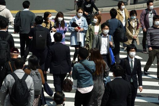People with protective masks cross a pedestrian walkway Thursday, April 9, 2020, in Tokyo. Japanese Prime Minister Shinzo Abe declared a state of emergency last Tuesday for Tokyo and six other prefectures to ramp up defenses against the spread of the coronavirus.
