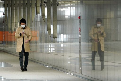 A man with protective mask walks on an underpass Thursday, April 9, 2020, in Tokyo. Japanese Prime Minister Shinzo Abe declared a state of emergency last Tuesday for Tokyo and six other prefectures to ramp up defenses against the spread of the coronavirus.