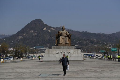 A man wearing a face mask walks at the Gwanghwamun Square in downtown Seoul, South Korea, Thursday, April 9, 2020. The new coronavirus causes mild or moderate symptoms for most people, but for some, especially older adults and people with existing health problems, it can cause more severe illness or death.