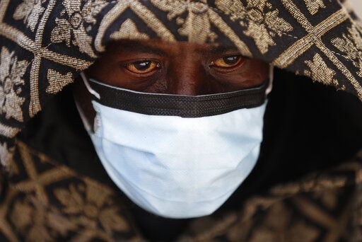 A man wears a protective mask while waiting for a bus in Detroit, Wednesday, April 8, 2020. Detroit buses will have surgical masks available to riders starting Wednesday, a new precaution the city is taking from the new coronavirus COVID-19.