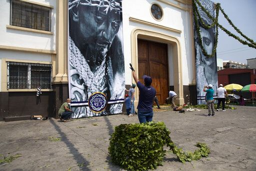 Cristo Rey brotherhood members hang banners with the images of Jesus Christ and Virgin Mary at the Candelaria church in Guatemala City, Wednesday, April 8, 2020. Catholics prepare to celebrate Holy Week amid measures to prevent the spread of the coronavirus, including stopping all religious activities across the country.