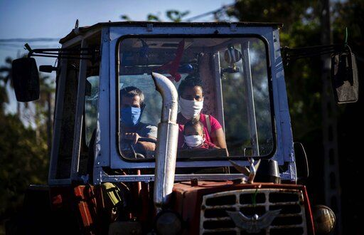 A family rides their tractor through the countryside wearing masks as a precaution against the spread of the new coronavirus in Havana, Cuba, Wednesday, April 8, 2020. Cuban authorities are requiring the use of masks for anyone outside their homes.