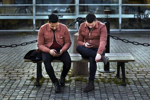 Two men check their phones as they sit near the harbor in Stockholm, Sweden, Wednesday, April 8, 2020. Swedish authorities have advised the public to practice social distancing because of the coronavirus pandemic, but still allow a large amount of personal freedom, unlike most other European countries. The new coronavirus causes mild or moderate symptoms for most people, but for some, especially older adults and people with existing health problems, it can cause more severe illness or death.