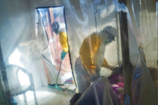 FILE - In this July 13, 2019 file photo, health workers wearing protective suits tend to an Ebola victim kept in an isolation cube in Beni, Congo. These African stories captured the world's attention in 2019 - and look to influence events on the continent in 2020.