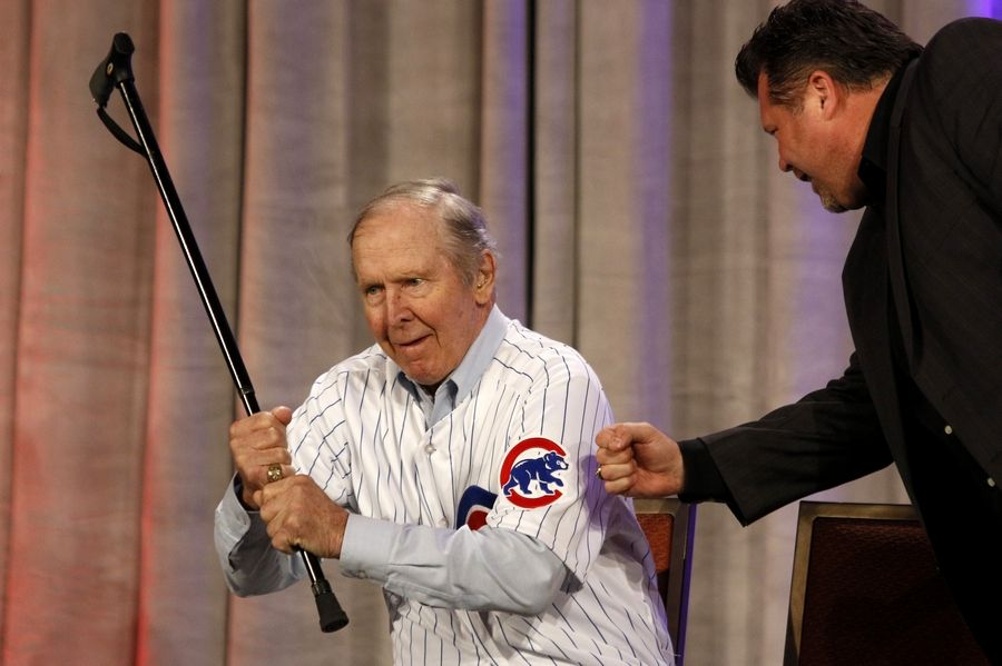Former Cub second baseman Glenn Beckert shows his batting grip with his cane as he gets a high-five from Ron Coomer during the annual Cubs Convention in January 2015.