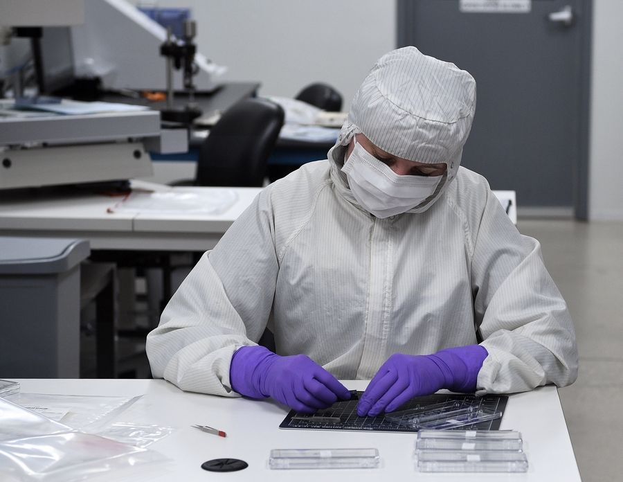 A worker in highly protective suit, gloves and mask works inside the clean room at Flexan in Lincolnshire, where production of medical devices to help meet the needs during the coronavirus are being ramped up at their factory.