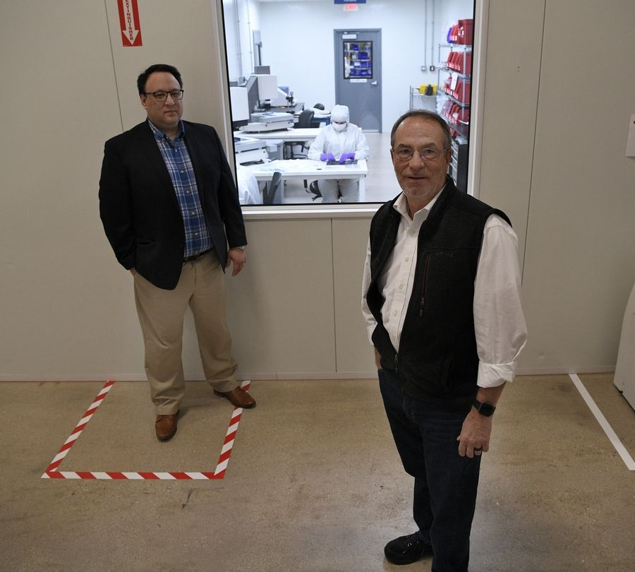 Harold Sant, Flexan vice president/general manager, left, and Tony Orsini, chief operating officer, stand near a clean room window as workers assemble medical devices.