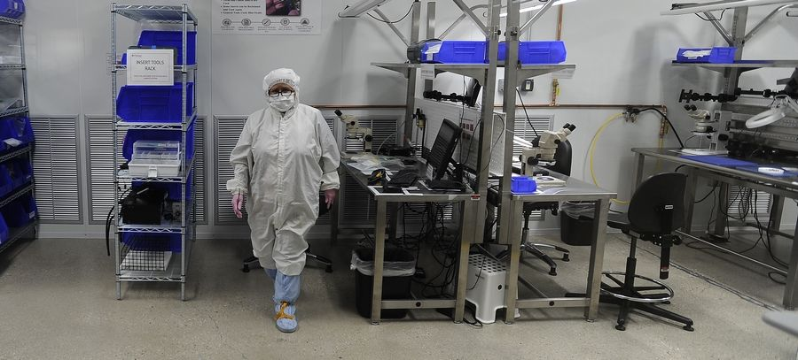 A worker in highly protected suit, gloves and mask works inside the clean room at Flexan in Lincolnshire where production of medical devices to help meet the needs during the coronavirus are being ramped up at their factory.
