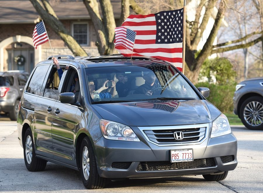 Families from the Saint James Catholic school and church in Arlington Heights held a drive-by parade for Illinois Army National Guard member Staff Sgt. Eric Gutzmer and his family Monday in Palatine. The Gutzmers attend the church and their children go to the school there.