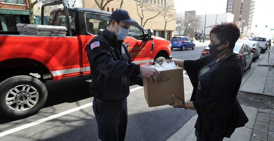Tameeca Russell, director of operations and programs at the Urban Muslim Minority Alliance, hands over a box of KN95 masks to firefighter/paramedic Brian Henderson of the North Chicago Fire Department. The organization donated hundreds of masks Monday to first responders and others.