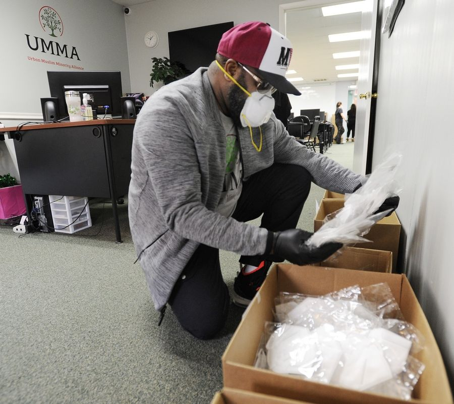 Hamaas Ibrahim, board president at the Urban Muslim Minority Alliance in Waukegan, sorts through boxes of KN95 masks Monday before they were donated to the North Chicago Fire Department and other fire and police departments in the area.