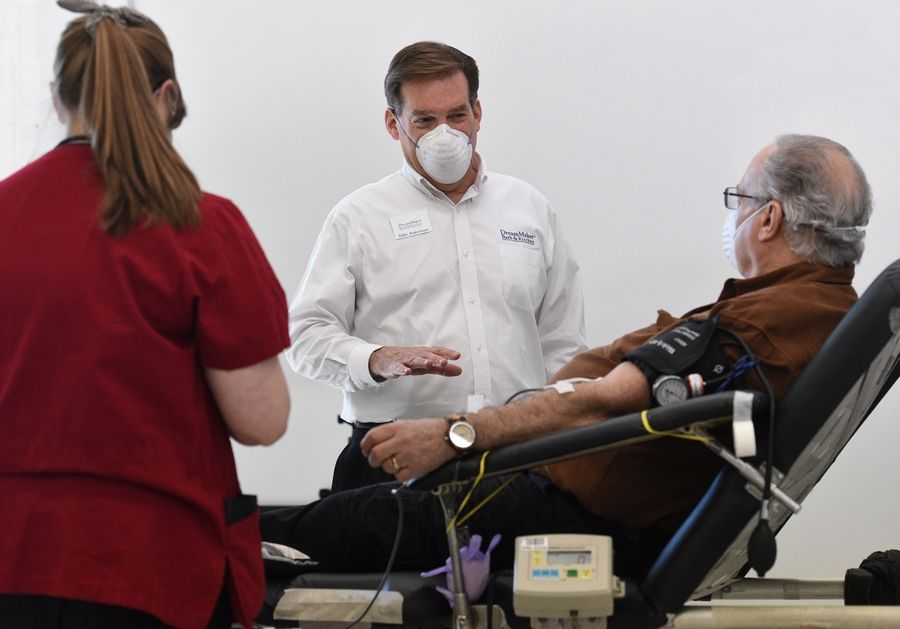 DreamMaker Bath & Kitchen CEO Mike Aukerman, center, talks with donor Yale Wolk of Lindenhurst during the American Red Cross blood drive Tuesday held at the Vernon Hills business.