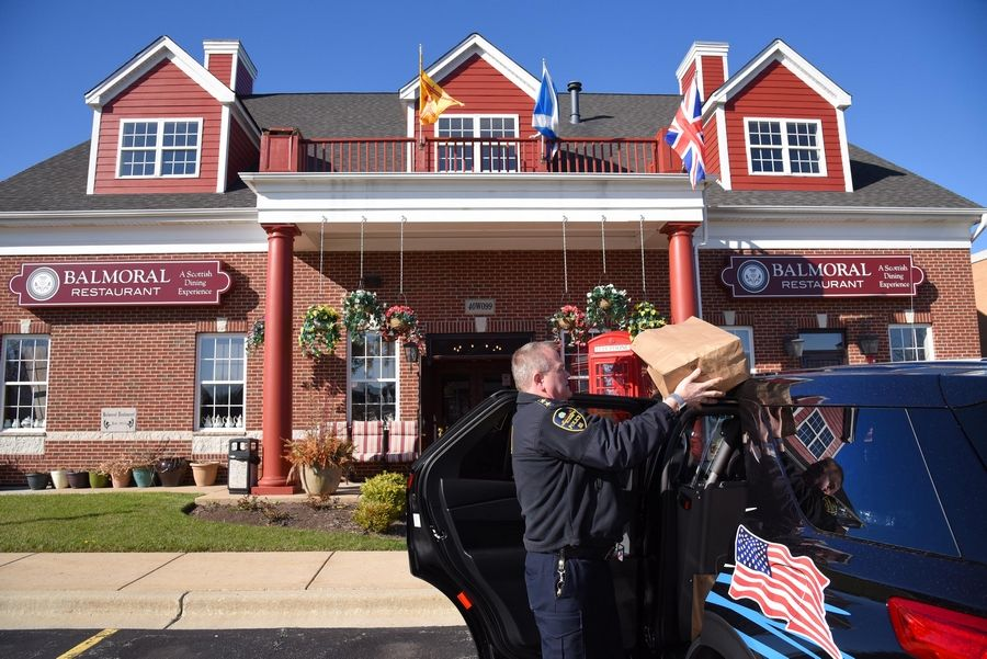 Campton Hills Police Chief Steve Millar takes donated meals from the roof of his car after picking them up from Balmoral Restaurant Tuesday evening. Owner Colin Smith donates one meal to a local family in need for every two meals he sells and Millar delivers them.