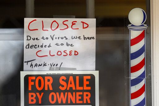 "FILE - In this April 2, 2020 file photo, ""For Sale By Owner"" and ""Closed Due to Virus"" signs are displayed in the window of a store in Grosse Pointe Woods, Mich. The second round of loan applications for the government's small business relief program has been slowed by computer issues at the Small Business Administration. Lenders complained Monday, April 27, that they couldn't get their applications into the SBA system known as ETran that processes and approves loans."