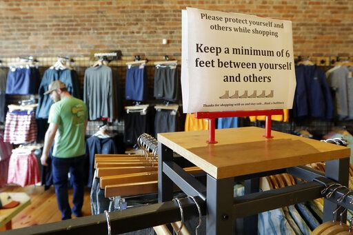 A sign reminding customers of social distancing is posted in the Bink's Outfitters store Wednesday, April 29, 2020, in Murfreesboro, Tenn. Retailers in 89 of Tennessee's 95 counties were allowed to reopen Wednesday with restrictions as the state begins the next wave of reopening its economy during the coronavirus pandemic.