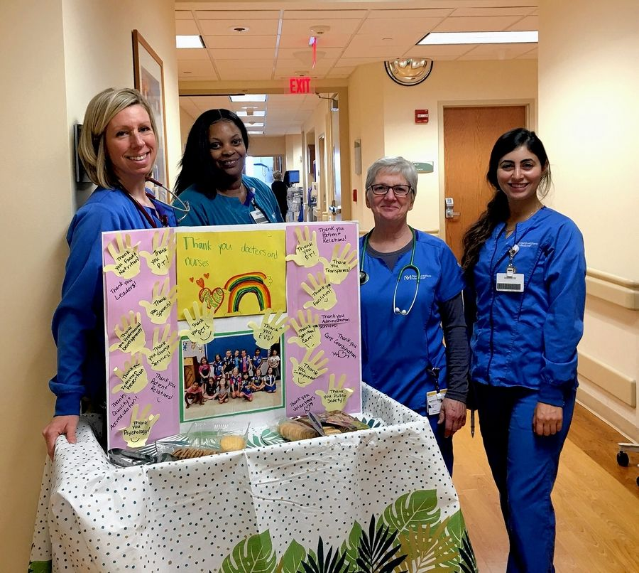 Staff members at Marianjoy Rehabilitation Hospital in Wheaton receive a donation of Girl Scout cookies and a giant thank you card from a Warrenville Girl Scout troop.