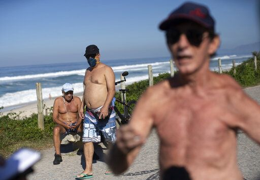 People, one wearing a mask, rest and exercise along the seafront next to Barra de Tijuca beach, as Fernando Ferreira, right, speaks during an interview as he takes a walk outside amid the new coronavirus pandemic in Rio de Janeiro, Brazil, Wednesday, April 29, 2020. The retired dentist and lawyer recommended reading the Bible and Albert Camus' The Plague, citing them as evidence pandemics have always happened to some degree, and said restrictions on commerce are 'œabsurd.'�